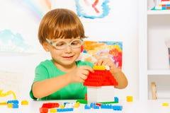 修建与块的聪明的小男孩 库存照片