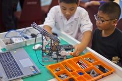 修建机器人的聪明的亚洲孩子 库存图片