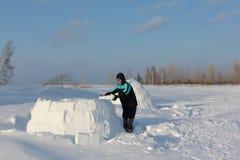 修建雪块的园屋顶的小屋人在冬天 免版税库存照片