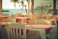 俯视地中海希腊的大阳台的传统希腊室外餐馆 在街道海的空的桌 库存照片