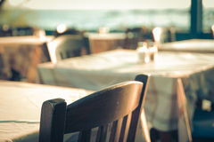 俯视地中海(希腊)的大阳台的传统希腊室外餐馆 在街道海的空的桌 免版税图库摄影