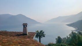 俯视朦胧的山和湖的铺磁砖的屋顶上面和棕榈树 库存照片