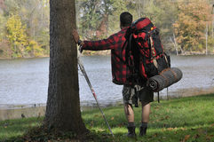 俯视池塘的背包徒步旅行者 免版税库存图片