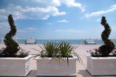 俯视海、白色楼梯栏杆、长凳和黄杨木潜叶虫的大阳台 免版税库存照片
