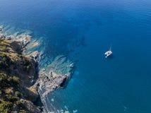 俯视海和一艘被停泊的筏,小船的峭壁的鸟瞰图 可西嘉岛 海岸线 法国 库存照片