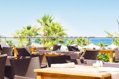 俯视海和棕榈树的室外餐馆 图库摄影