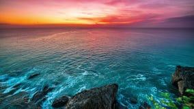 俯视海洋和岩石在巴厘岛海岛上的难以置信的日落timelapse在印度尼西亚 股票录像