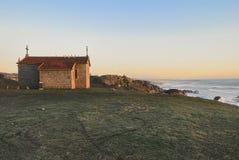 俯视海洋的教堂在日落 免版税库存图片
