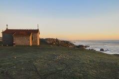 俯视海洋的教堂在日落 库存图片