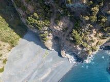 俯视海,黑海滩, Nonza的自治市,盖帽Corse,可西嘉岛半岛的峭壁的鸟瞰图  库存照片