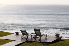 俯视海洋的松弛椅子 免版税图库摄影