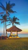 俯视海洋的海滩小屋在日落 库存照片