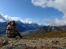俯视阿拉斯加的谷的背包徒步旅行者 免版税库存图片