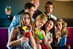 俱乐部或棒饮用的鸡尾酒的人们 免版税库存图片