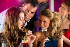 俱乐部或棒饮用的鸡尾酒的人们 免版税库存照片