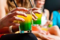 俱乐部或迪斯科饮用的鸡尾酒的妇女 免版税库存照片
