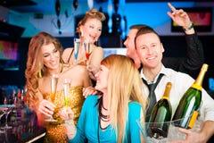 俱乐部或酒吧饮用的香槟的人们 免版税库存图片