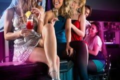 俱乐部或酒吧饮用的鸡尾酒的人们 免版税库存图片