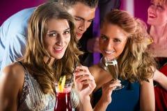 俱乐部或酒吧饮用的鸡尾酒的人们 免版税库存照片