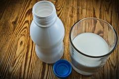 倒一个小的瓶牛奶和一杯在木桌上的牛奶 免版税库存图片