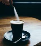 倒一个香囊糖到咖啡馆拿铁里 免版税库存照片