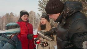 倒从热水瓶烧瓶的父亲热的茶家庭的在冬天步行在森林里 股票录像