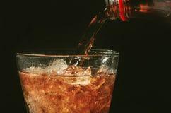 倒从瓶的可乐到在黑色的玻璃和泡影苏打 免版税库存图片