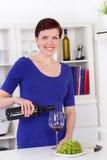 倒在一块玻璃的少妇红葡萄酒在她的厨房里 免版税库存图片