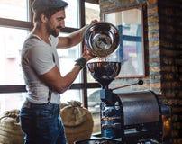 倒在咖啡烘烤器的行家未加工的咖啡豆 免版税图库摄影