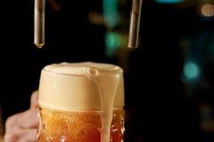 倒在夜总会的男服务员新鲜的啤酒 免版税库存图片