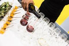 倒在玻璃的女服务员红葡萄酒在与白色的自助餐桌上 免版税库存照片