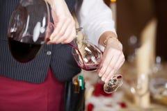 倒在葡萄酒杯的女服务员红葡萄酒从蒸馏瓶 库存图片