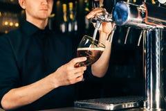 倒在轻拍的侍酒者的手一个大储藏啤酒在餐馆或客栈 免版税库存图片