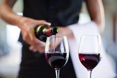 倒在玻璃的女服务员的中间部分红葡萄酒 库存照片
