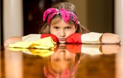 翻倒女孩画象擦亮桌的红色橡胶手套的 免版税库存照片