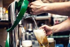 倒或酿造桶装啤酒的男服务员在餐馆,酒吧 免版税库存图片