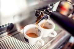 倒新鲜的咖啡的煮浓咖啡器入杯子在餐馆 做咖啡的咖啡自动机器 免版税库存照片
