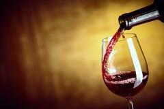 倒杯从瓶的红葡萄酒 库存图片