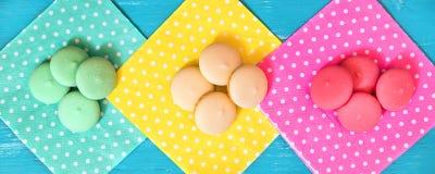 倒栽跳水、五颜六色的macarons或者饼干在另外被加点的餐巾 免版税库存图片