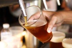 倒桶装啤酒的啤酒轻拍 免版税图库摄影