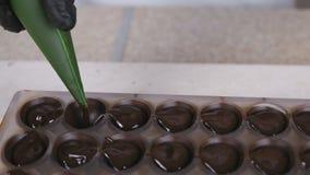倒液体巧克力填装的果仁糖以从酥皮点心袋子的形式的贝克的手 影视素材