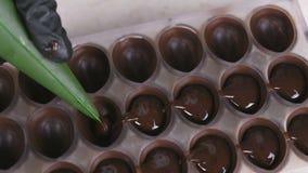 倒液体巧克力填装的果仁糖以从酥皮点心袋子的形式的贝克的手 股票视频