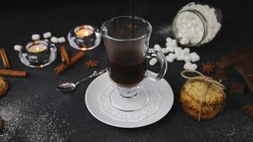 倒热巧克力电影用蛋白软糖到玻璃里 与蜡烛的美好的背景,八角茴香属,自创曲奇饼 股票录像