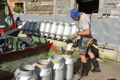 倒牛奶的工作者入坦克在农舍 免版税库存图片