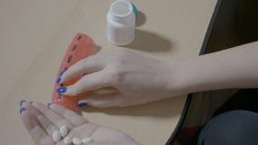 倒空一个瓶sliming的药片和在家安排他们的妇女女性经理在每日组织者计划者箱子- 股票视频