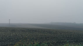 倒空与定向塔的黑土壤领域在大雾 库存照片