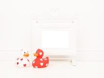 倒空与空间的白色在一个白色客厅设置的画框文本的或愿望与一只红色和一只白色橡胶鸭子 免版税库存照片