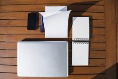 倒空与蓝色圆珠笔的白色笔记薄和手机和膝上型计算机 免版税库存照片