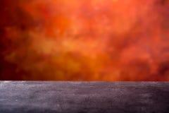倒空具体桌和抽象蜡染布橙红背景准备好集锦照相 您的产品的空的空间 库存照片