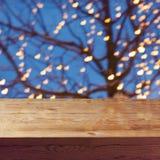倒空在夜光装饰和树背景的木桌 免版税库存图片